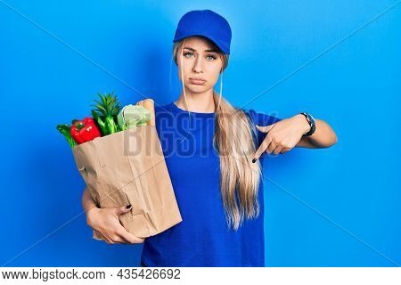 Young caucasian woman wearing courier uniform with groceries from supermarket pointing down looking sad and upset, indicating direction with fingers, unhappy and depressed.