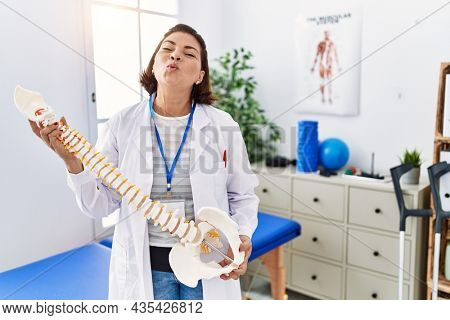 Middle age hispanic physiotherapy woman holding anatomical model of spinal column looking at the camera blowing a kiss being lovely and sexy. love expression.