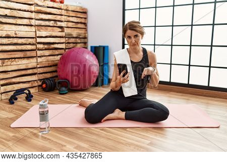 Middle age woman sitting on training mat at the gym using smartphone pointing down looking sad and upset, indicating direction with fingers, unhappy and depressed.