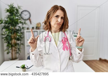 Middle age doctor woman wearing pink cancer ribbon on uniform pointing up looking sad and upset, indicating direction with fingers, unhappy and depressed.