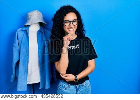 Young hispanic woman with curly hair wearing staff t shirt annoyed and frustrated shouting with anger, yelling crazy with anger and hand raised