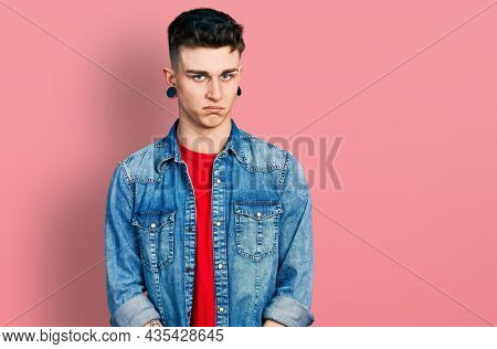 Young caucasian boy with ears dilation wearing casual denim jacket skeptic and nervous, frowning upset because of problem. negative person.