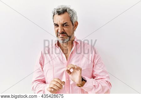 Middle age hispanic man standing over isolated background disgusted expression, displeased and fearful doing disgust face because aversion reaction. with hands raised
