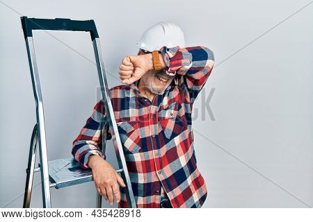 Handsome mature handyman close to construction stairs wearing hardhat smiling cheerful playing peek a boo with hands showing face. surprised and exited