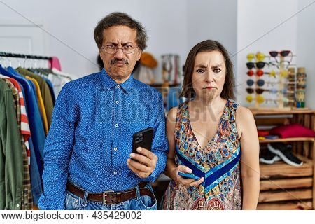 Middle age interracial couple at retail shop using smartphone skeptic and nervous, frowning upset because of problem. negative person.