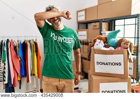 Middle age hispanic man wearing volunteer t shirt at donations stand smiling cheerful playing peek a boo with hands showing face. surprised and exited