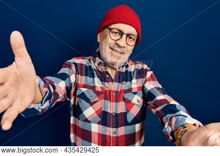 Handsome mature man wearing hipster look with wool cap looking at the camera smiling with open arms for hug. cheerful expression embracing happiness.