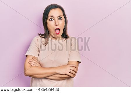 Middle age hispanic woman with arms crossed gesture afraid and shocked with surprise and amazed expression, fear and excited face.