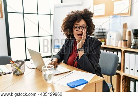 African american woman with afro hair working at the office wearing operator headset hand on mouth telling secret rumor, whispering malicious talk conversation
