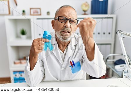 Mature doctor man holding blue ribbon at the clinic annoyed and frustrated shouting with anger, yelling with anger and hand raised