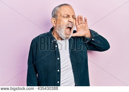 Handsome senior man with beard wearing casual denim shirt shouting and screaming loud to side with hand on mouth. communication concept.
