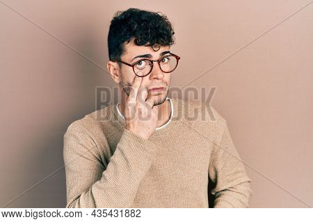 Young hispanic man wearing casual clothes and glasses pointing to the eye watching you gesture, suspicious expression