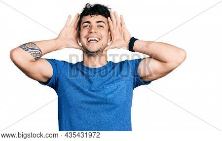 Young hispanic man wearing casual t shirt smiling cheerful playing peek a boo with hands showing face. surprised and exited