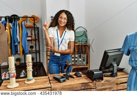 Beautiful hispanic woman working at clothing shop smiling with happy face winking at the camera doing victory sign. number two.