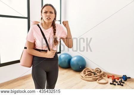 Young beautiful woman at the gym wearing sportswear holding yoga mat annoyed and frustrated shouting with anger, yelling crazy with anger and hand raised