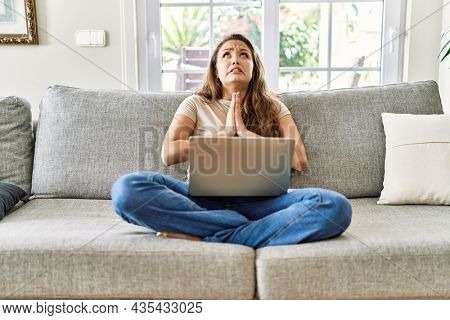 Beautiful young brunette woman sitting on the sofa using computer laptop at home begging and praying with hands together with hope expression on face very emotional and worried. begging.