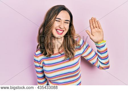 Young hispanic girl wearing casual clothes waiving saying hello happy and smiling, friendly welcome gesture