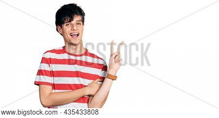 Handsome hipster young man wearing casual striped t shirt smiling with happy face winking at the camera doing victory sign. number two.