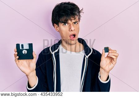 Handsome hipster young man holding floppy disk and sdxc card in shock face, looking skeptical and sarcastic, surprised with open mouth