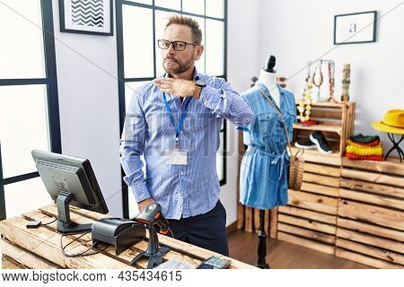 Middle age man working as manager at retail boutique cutting throat with hand as knife, threaten aggression with furious violence