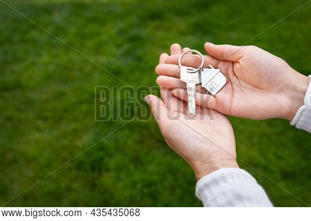 Keys With A Keychain In The Form Of A Metal House From A New House Or Apartment In The Hands Of A Gi