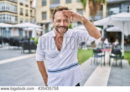 Middle age man outdoor at the city very happy and smiling looking far away with hand over head. searching concept.