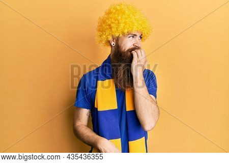 Redhead man with long beard football hooligan cheering game wearing funny wig looking stressed and nervous with hands on mouth biting nails. anxiety problem.