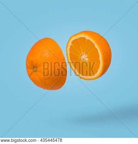 Juicy Orange  Cut In Two Halves Flying In The Air On A Blue  Background. Summer Citrus Fruit Refresh