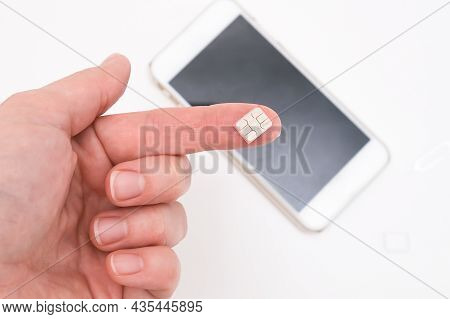 Micro Sim Card For Mobile Communication On A Finger Close Up, Wireless Connection Concept
