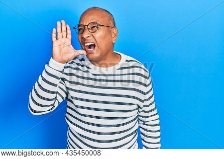 Middle age latin man wearing casual clothes and glasses shouting and screaming loud to side with hand on mouth. communication concept.