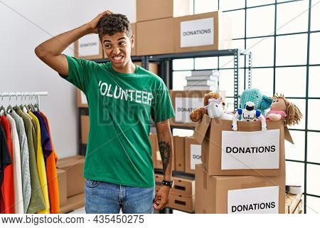 Young handsome hispanic man wearing volunteer t shirt at donations stand confuse and wondering about question. uncertain with doubt, thinking with hand on head. pensive concept.