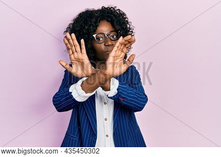 Young african american woman wearing business clothes and glasses rejection expression crossing arms and palms doing negative sign, angry face