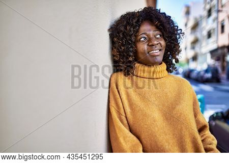 African american woman smiling confident leaning on wall at street