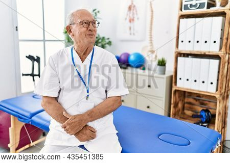 Senior physiotherapy man working at pain recovery clinic smiling looking to the side and staring away thinking.