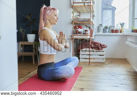 Sportswoman With Ponytail Holds Hands In Namaste Sitting In Lotus Pose Indoors