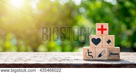 Wooden Block With Icon Healthcare Medical With Copy Space On Green Blurred Backgrounds, Concept Of I
