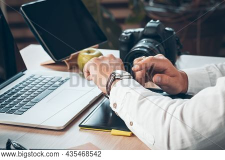 Young Man Photographer Working On A Computer. Work Desk With Keyboard, Camera, Laptop And Lenses.