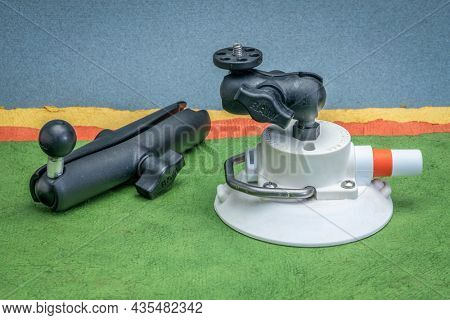 Fort Collins, CO, USA - October 6, 2021: RAM camera mount with extension and suction cup by SeaSucker against abstract paper landscape, accessories for sport and adventure photography.