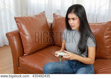 Vdo Game Console Station Concept. Active Asian Woman Sitting On Sofa, Holding Joystick And Playing E