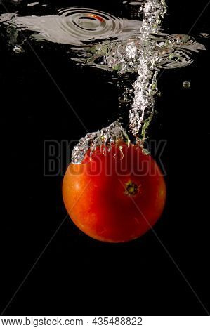 Ripe Tomato Falls Deeply Under Water With A Big Splash