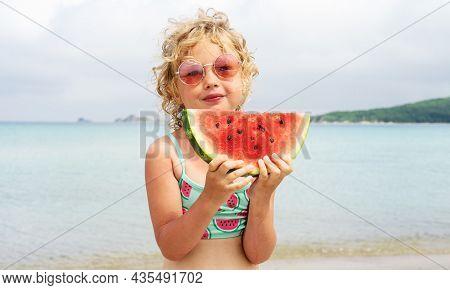 Portrait Little Girl Licking Fresh Watermelon Slice Posing On Beach Having Fun And Positive Emotion