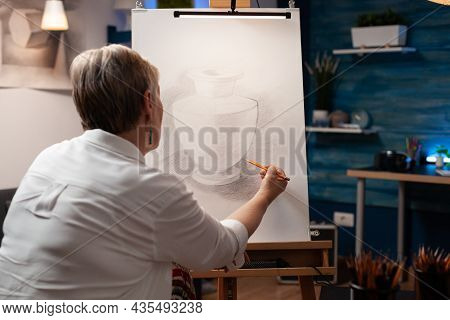 Close Up Of Elderly Woman Drawing Vase On Canvas With Pencil In Workshop Studio. Caucasian Senior Ar