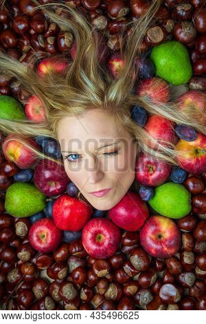 Portrait, Head Of Young Beauty Caucasian Woman With Blonde Hair Blinking From Fruit And Chestnut Bac