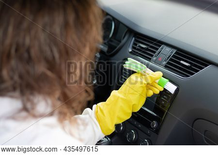 A Girl In Yellow Rubber Gloves Wipes The Dashboard Of A Car From Dust With A Special Brush On A Brig