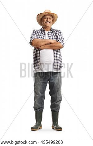 Full length portrait of a mature farmer smiling and posing with crossed arms isolated on white background