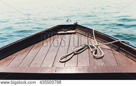 Closeup Of Old Boat Front Wooden Brown Deck With Blue Sea In The Background And Anchoring Rope