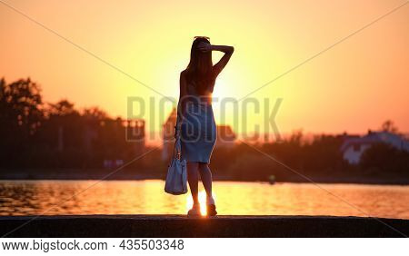 Rear View Of Lonely Woman Standing Alone On Lake Shore On Warm Evening. Solitude And Relaxing In Nat
