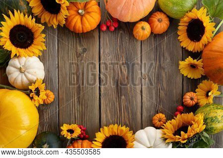 Thanksgiving Framework. Flowers, Pumpkins And Fallen Leaves On Wooden Background. Copy Space For Tex