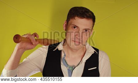 Man On Strict Face Posing With Wooden Bat. A Man In A Business Strict Elegant Suit With A Wooden Bat