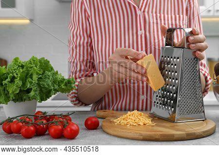Woman Grating Cheese At Kitchen Table, Closeup